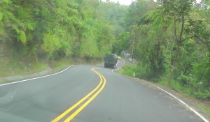 We are driving down a very scenic, winding, and steep hill. That is the guard house ahead on the right.