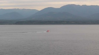 The pilot boat looks small against the hills in the background.