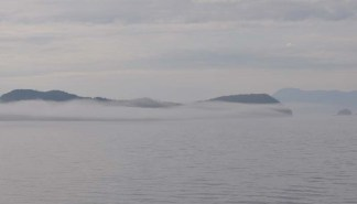 Fog rolls over the water and the hills peek through it.
