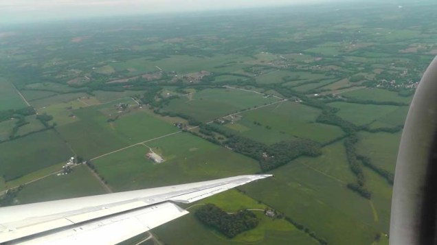 Flying into Kansas, the green farmland below.