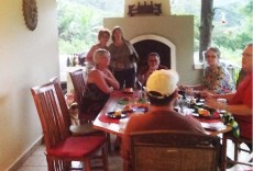 The dinner crowd, Holly and I in front of the fireplace, Cindy and her husband in front of us, Scott in the white hat at the other end of the table, Jerry and Jennifer on the right. My husband Joel is behind the camera taking photos on his iPad.