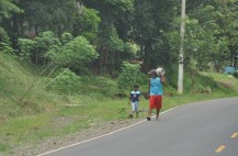 A guy with a gas can on his shoulder walks along with his little boy.