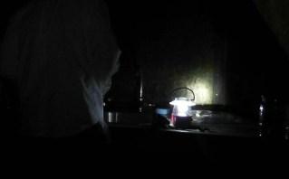 Joel brushes his teeth by lantern light.