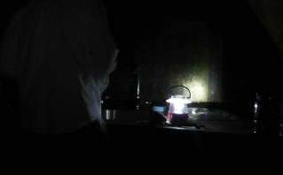 Joel brushes his teeth by lantern light.