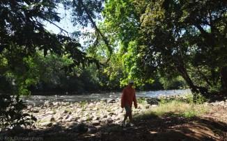 Joel walking on the river bank.