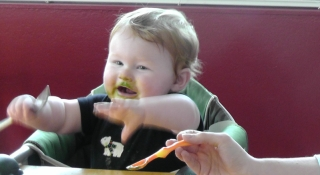I am eating veggies and playing with my own spoon.