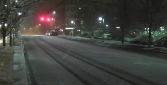 The snow is starting to stick on the roads as the temperature drops below freezing.