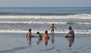 Children play in the surf.