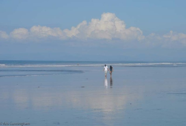A couple walks on the wet sand while our friends body surf in the distance.
