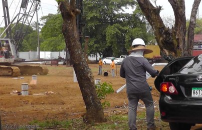 At the construction site down the street this guy has his hard hat on over his straw sun hat.