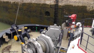 We are secured to the tug, and it is secured to the side of the lock. The man keeps a close eye on the controls, adjusting the ropes to keep the tension right and to keep our positions in the lock as the water rises, taking us up with it.