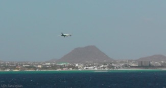 An airplane comes in for a landing as we leave the island behind.