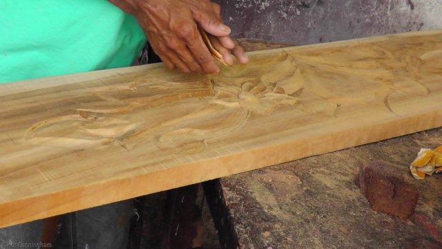 This man was working on a headboard for a bed with carvings of flowers and leaves.