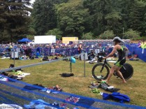 Many wet suits are now hanging on the lines as swimmers have left on their bicycles. One of the leaders has completed his bike ride here and is going to grab his running shoes. The bicycles had pedals that clipped to shoes, and many contestants left their shoes clipped to the bike pedals to make the changes faster.