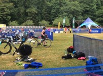 Another contestant has finished swimming and is leaving on her bicycle. There were a total of 1400 people participating in both races lengths and groups left about every 10 minutes so soon there were people in every stage of the race in the transition area.
