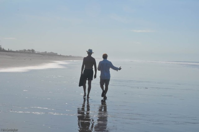 two friends walk down the beach