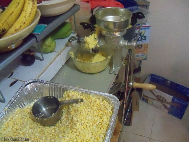 grinding the corn into a yellow mush