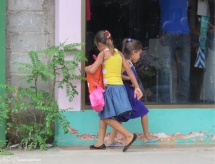 These girls play and dance on the sidewalk while they follow their mother on her errands.