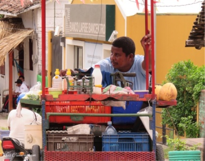 A working guy struggles to push his cart up hill so he can sell his juice and snacks to the midday street traffic.