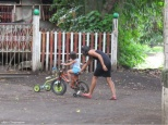A mom teaches her little girl to ride a bicycle.
