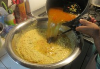 Adding broth to the corn. Cedo says it must be warm because it results in fluffier and softer corn.