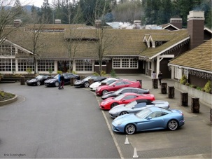 The parking lot has a Mazerati, an Aston Martin, six Ferarris, and one lowly Cadillac