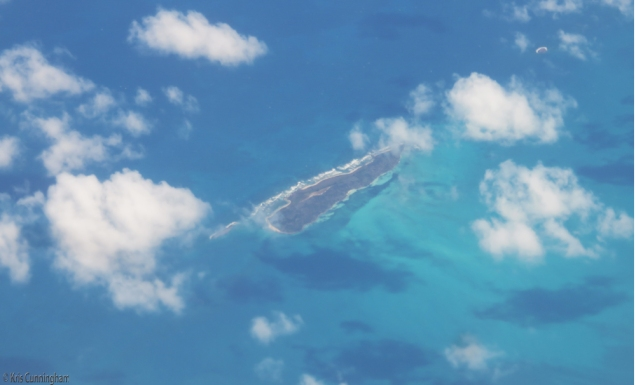 This island appears to be floating on the top of the water because of the shadows below.