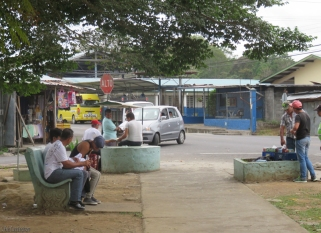 There were people relaxing in the town park, and that looks like a school across the street.