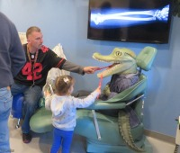 There is a dentist office. Here a dad was helping his kid brush all those alligator teeth.