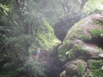 A hiker makes her way up the slippery rocks