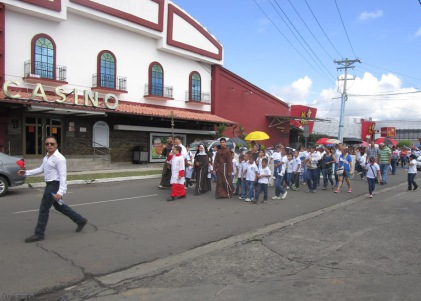 The religious parade passes in front of a casino.