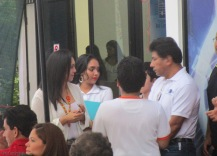 Victor Chirú (right) and the wife of José Cáceres (left with an orange necklace) confer on the upcoming activities.