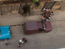 looking down from our balcony as a vendor walks down the street, and men play on the sidewalk