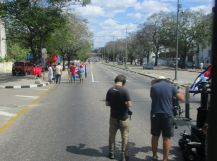 A protest in the street, people waving flags and signs, and a film crew recording the event