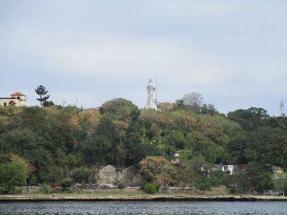 a very large Jesus statue on the other side of the water