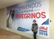 Haydee in front of a welcome sign for the world youth event